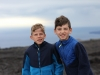 Alex and Evan bracing against the wind at Volcanoes National Park